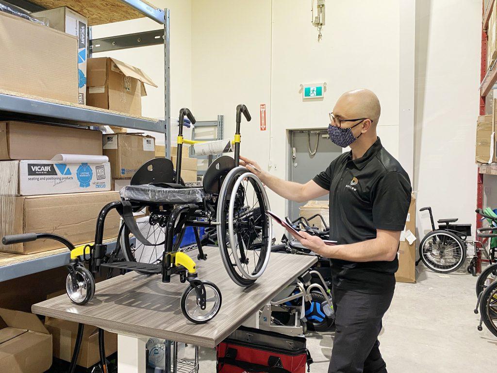 Man inspecting a wheelchair