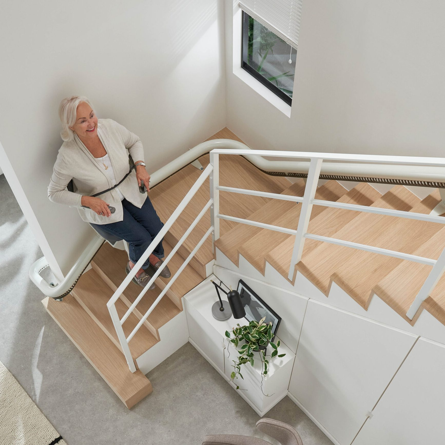 Woman using stairlift independently in a home setting.
