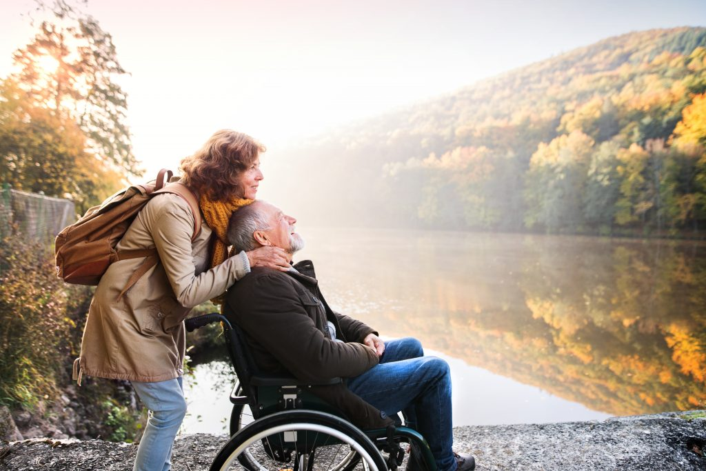 Senior man by lake with with wife embracing him.