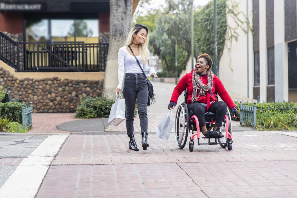 Woman in wheelchair crossing the street with friend