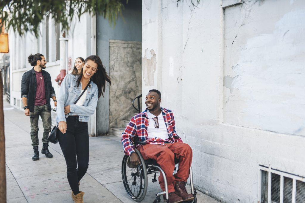 Young man in wheelchair with friend to right walking in town