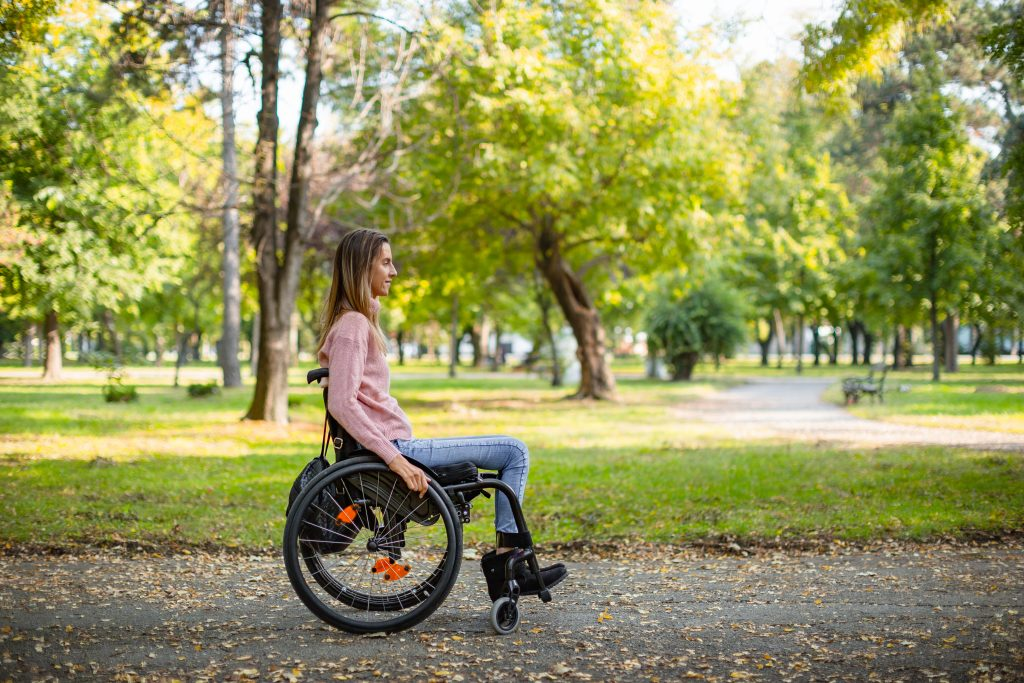 Young woman in wheelchair in park