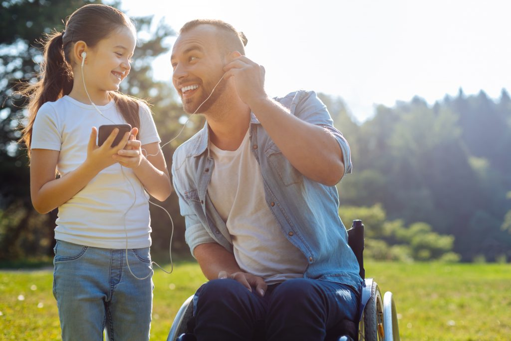 Young dad in wheelchair listening to iPod with daughter by sharing headphones in the park
